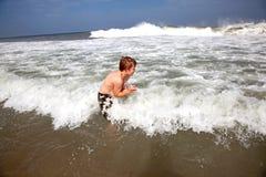 Мальчик имеет потеху в выключателях океана стоковые фотографии rf