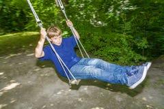 Мальчик имеет потеху идя на качания Стоковая Фотография