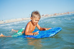 Мальчик имеет потеху с surfboard Стоковые Фотографии RF
