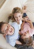 Мальчик имея потеху с матерью и сестрой на софе Стоковые Изображения RF