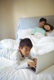 Мальчик используя компьтер-книжку в спальне Стоковая Фотография RF
