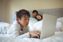 Мальчик используя компьтер-книжку в спальне Стоковые Фото
