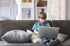 Мальчик используя компьтер-книжку на софе дома Стоковые Изображения RF