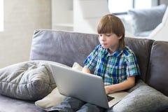 Мальчик используя компьтер-книжку на софе дома Стоковая Фотография