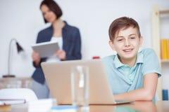 Мальчик используя компьтер-книжку дома Стоковое фото RF
