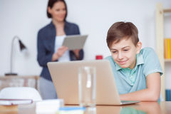 Мальчик используя компьтер-книжку дома Стоковая Фотография