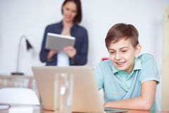 Мальчик используя компьтер-книжку дома Стоковое Изображение RF
