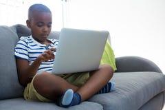 Мальчик используя компьтер-книжку пока сидящ с пересеченное шагающим на софе дома Стоковая Фотография