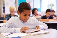Мальчик используя планшет в классе начальной школы Стоковое Фото