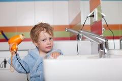 Мальчик используя фен для волос в ванной комнате стоковое фото rf