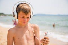 Мальчик используя smartphone на летний день пляжа Стоковые Фото