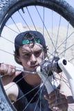 Мальчик исправляя колесо велосипеда BMX Стоковая Фотография RF