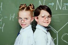 Мальчик и девушка в белых пальто и защитных eyeglasses стоя совместно около доски и усмехаясь на камере Стоковая Фотография RF