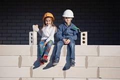 Мальчик и девушка в доме строения шлемов стоковые фотографии rf