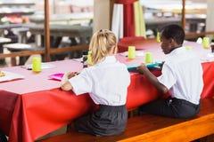 Мальчик и девушка в школьных формах имея обед в школьном кафетерии стоковые фотографии rf