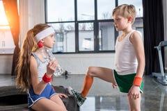 Мальчик и девушка в sportswear говоря на студии фитнеса Стоковое фото RF