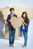 Мальчик и девушка держа сердце картона человек влюбленности поцелуя принципиальной схемы к женщине Стоковые Фотографии RF