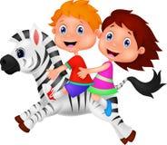 Мальчик и девушка ехать зебра Стоковые Фотографии RF