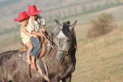 Мальчик и девушка ехать лошадь на ферме Стоковые Фото