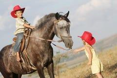 Мальчик и девушка ехать лошадь на ферме Стоковые Фотографии RF