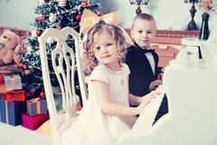 Мальчик и девушка играя рояль стоковое фото rf
