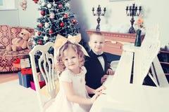 Мальчик и девушка играя рояль стоковые изображения rf