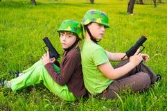 Мальчик и девушка играя солдат Стоковые Фото
