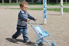 Мальчик и девушка играя с детскими дорожными колясками. Стоковая Фотография