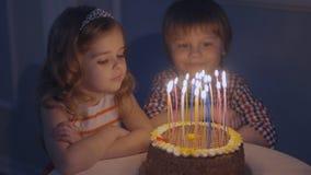Мальчик и девушка на праздничном торте смотрят свечи и делают желания, тогда дуют вне свечи на торте сток-видео