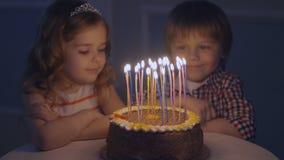 Мальчик и девушка на праздничном торте смотрят свечи и делают желания, тогда дуют вне свечи на торте акции видеоматериалы