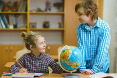 Мальчик и девушка на уроке землеведения в классе школы принципиальная схема воспитательная Стоковое фото RF