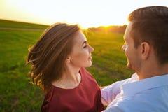 Мальчик и девушка обнимая игру на заходе солнца Влюбленность романтичная Стоковая Фотография RF
