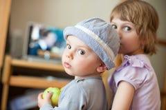 Мальчик и девушка повернули вокруг смотреть через их плеча Стоковые Фотографии RF