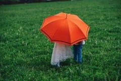 Мальчик и девушка под красным зонтиком Стоковые Фотографии RF