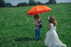 Мальчик и девушка под красным зонтиком Стоковая Фотография