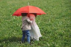 Мальчик и девушка под красным зонтиком Стоковое фото RF