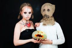 Мальчик и девушка при состав хеллоуина держа тыкву Стоковые Изображения