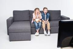 Мальчик и девушка сидя на софе и смотря ТВ совместно Стоковые Изображения RF
