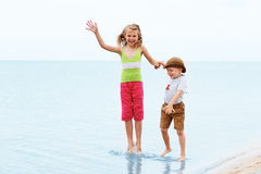 Мальчик и девушка скача и имея потеха взволнованности положительные Стоковая Фотография