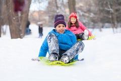 Мальчик и девушка сползая на розвальни в парке Стоковое Изображение RF