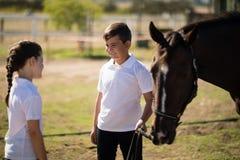 Мальчик и девушка стоя с лошадью и говорить стоковое изображение rf