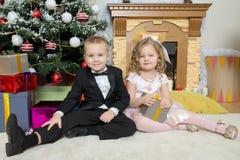 Мальчик и девушка с подарками около рождественской елки стоковая фотография