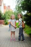 Мальчик и девушка с руками владением schoolbags Стоковое Изображение