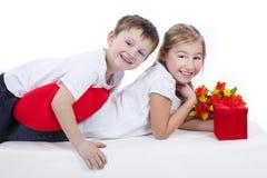 Мальчик и девушка с цветками и подарочной коробкой стоковая фотография