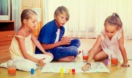 Мальчик и 2 девушки играя на настольной игре внутри помещения Стоковая Фотография