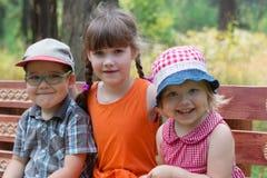 Мальчик и 2 девушки сидят на стенде и улыбках на солнечном Стоковая Фотография