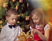 Мальчик и девушки сидя на софе Стоковое фото RF