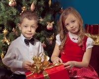 Мальчик и девушки сидя на софе Стоковое Изображение RF