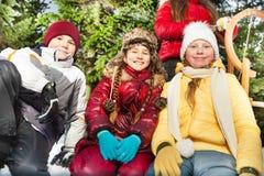 Мальчик и девушки сидя совместно снаружи в снеге Стоковое Изображение