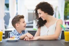 Мальчик и его десерт дегустации матери с соком в ресторане курорта внешнем стоковая фотография